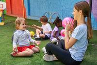 Sportlehrerin spielt mit Kindern Ball draußen vor der Kita