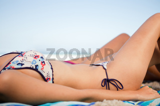 Side view of a young woman bikini on the beach
