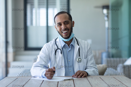 Portrait of mixed race male doctor wearing face mask looking at the camera and smiling