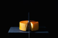 Big round of hard cheese with knife