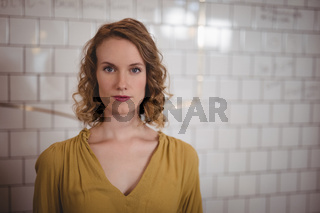 Portrait of confident beautiful woman standing against white wall