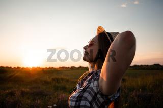 Girl in hat enjoying warm summer evening