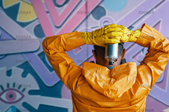 Cropped image of street artist with spray paint can in hand standing near the wall