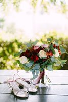bridal bouquet of white and red roses, peonies, branches of eucalypt tree, alstroemeria and chrysantemum with white and maroon ribbons, shoes of the bride near it