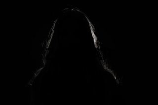 anonymous woman hiding face and identy in the dark shadow