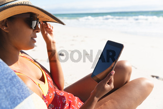 Mixed race woman on beach holiday sitting in deckchair using tablet
