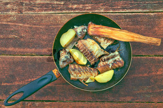 Fried fish and potatoes in frying pan