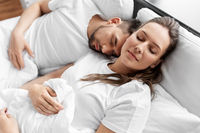 happy couple sleeping in bed at home