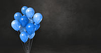 Blue balloons bunch on a black wall background. Horizontal banner.
