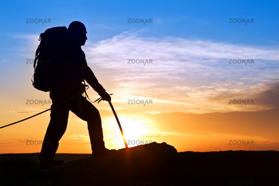 Silhouette of the rock-climber on background sunrising