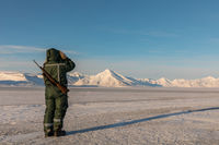 Man with a rifle and binoculars in arctic landscape at Svalbard