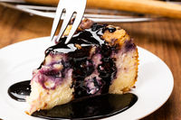 Using metal fork taking a bite from a piece of homemade blueberry and crumble cheesecake topping with chocolate.