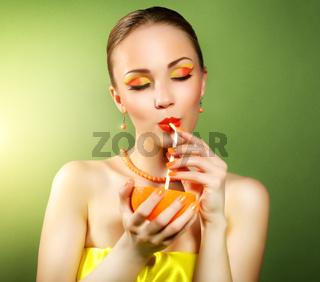 Girl with beautiful make-up holding orange fruit