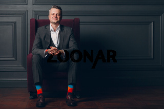 Portrait of smiling senior middle adult man in gray suit and colorful multi colored socks looking at camera with copy space