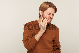 Dental health problems. Portrait of bearded man in sweatshirt holding sore cheek, frowning from acute tooth pain