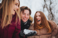 Happy best friends teenagers enjoying cold winter weather and first snow while having fun outdoor