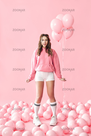 Full length portrait of trendy surprised girl with pink balloons on pink pastel background
