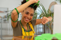 Happy mixed race woman celebrating st patrick's day making video call and dancing