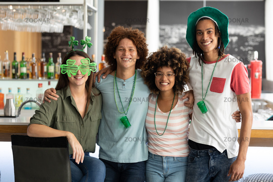 Portrait of diverse group of happy friends celebrating st patrick's day embracing at a bar