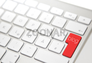 White computer keyboard with red 'blog' button