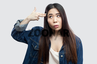 Emotional asian young woman on gray background.