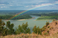 Rainbow with clouds over a river valley