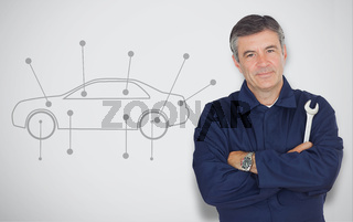 Mature mechanic standing next to car diagram