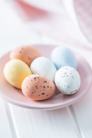 Chocolate easter eggs. Sweet candy eggs on pink plate.