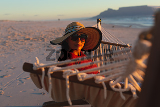 Portrait of happy mixed race woman on beach holiday looking to camera sitting in hammock at sunset