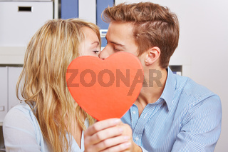 Paar küsst sich hinter einem roten Herz