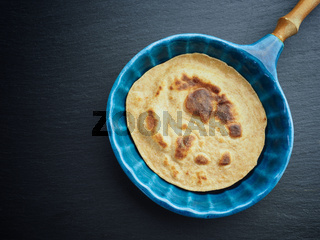 Delicious spelt pancake in a blue stoneware pan, too view