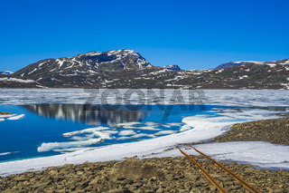 Old rails lead into water of frozen lake Vavatn Hemsedal.