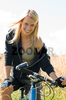 Mountain biking young woman sportive sunny meadows