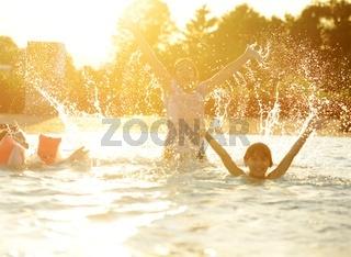 Happy children together splashing water