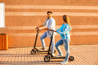The young couple spend time together riding electric scooter in the city