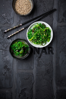 Traditional Japanese wakame salad with sesame seeds on black background. Healthy and fresh seaweed salad.