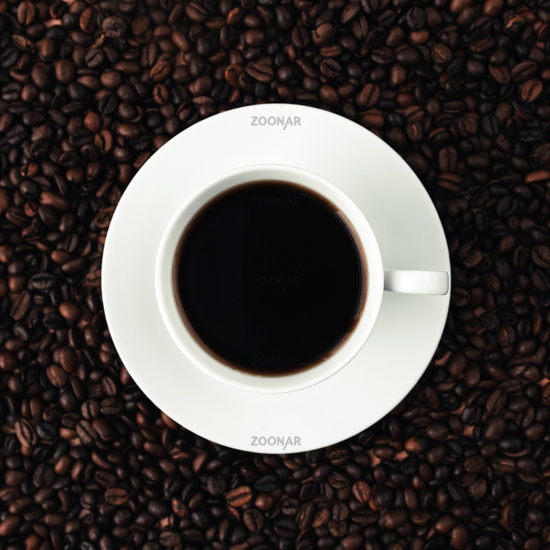White plate, cup of coffee on a bunch of roasted coffee beans background