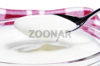 joghurt auf einem löffel über einer schale auf einem tuch