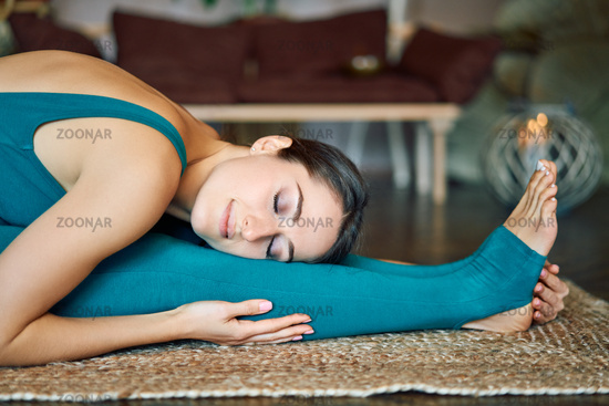 Young calm woman practicing yoga at home doing seated forward bend asana