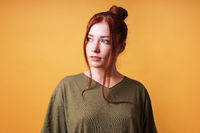 portrait of pretty young woman with red hair bun looking away