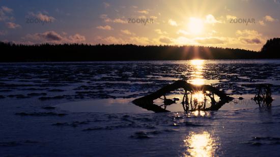 dim sun of winter sunset over frozen lake