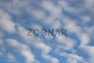 Full frame image of fluffy white clouds in mid blue sky