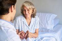 Arzt oder Krankenpfleger hält die Hände einer Seniorin