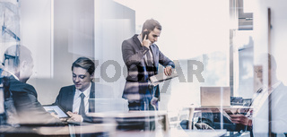 Businessman talking on a mobile phone on corporate office.