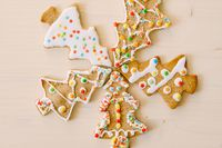 Five herringbone gingerbread cookies, differently decorated with glaze and sprinkles, set against a white painted wood texture.