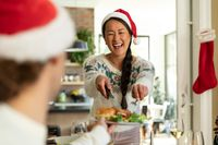 Happy asian woman in santa hat celebrating christmas with friends at home