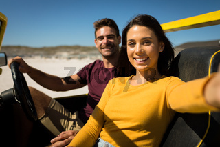 Caucasian couple on a beach buggy by the sea taking selfie