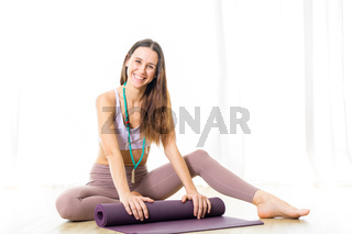 Young sporty female yoga instructor in bright white yoga studio, smiling cheerfully while rolling the yoga mat after yoga session.