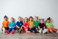Cheerful children sitting on a floor near the wall