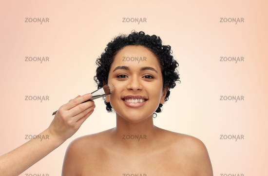 happy woman and hand of make up artist with brush